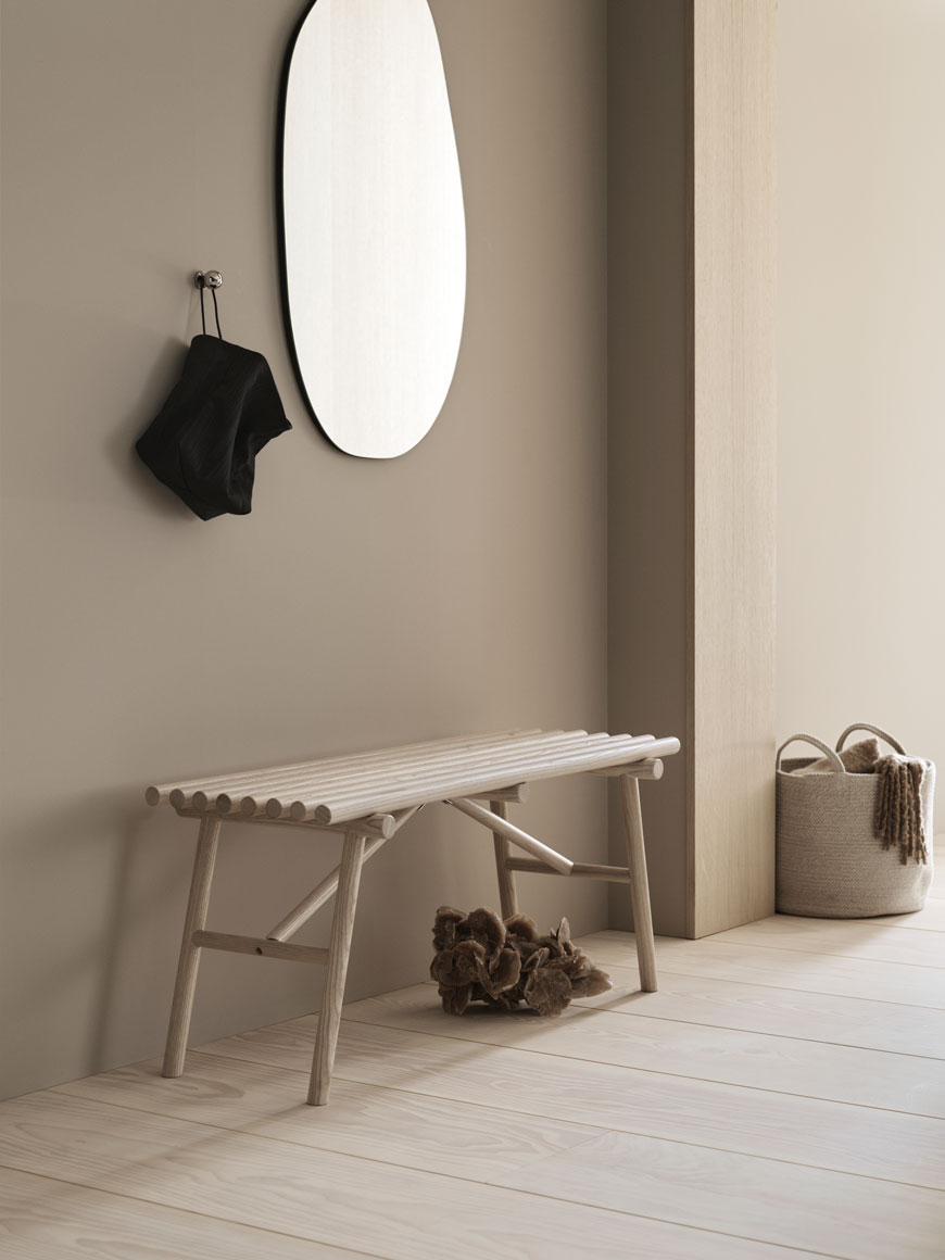A pale ash wood bench sits underneath an organically shaped mirror for H&M Home.