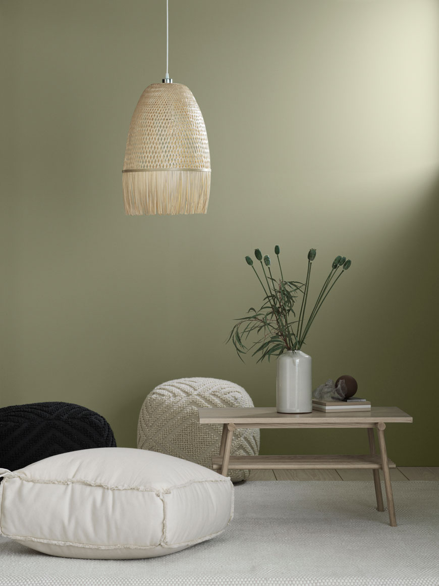 Soothing, natural home accessories styled in a with a soft green living room with a low level rattan pendant lamp.