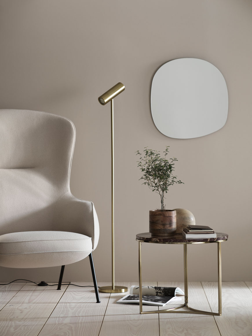 Striking contemporary brass floor lamp and cherry marble coffee table in a minimalist living room.