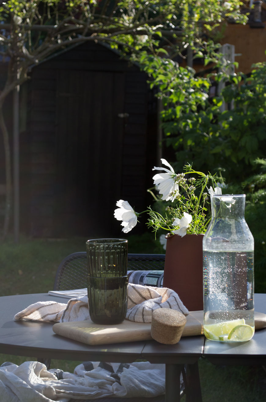 A light drenched table in the garden set with glasses, a pitcher full of white flowers and linen napkins.