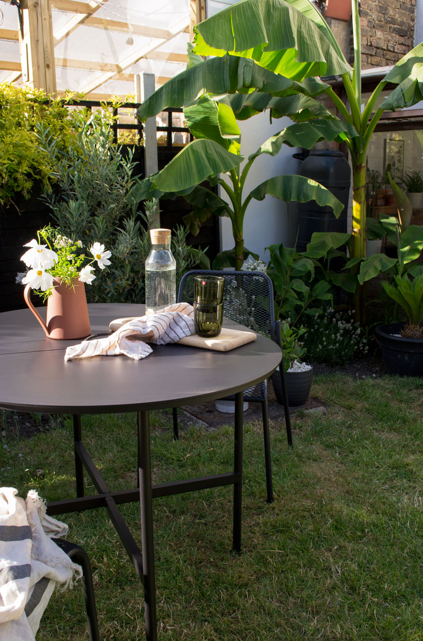 A stylish table and chairs in front of tropical banana trees shows how to make the garden feel like an extension of your home.