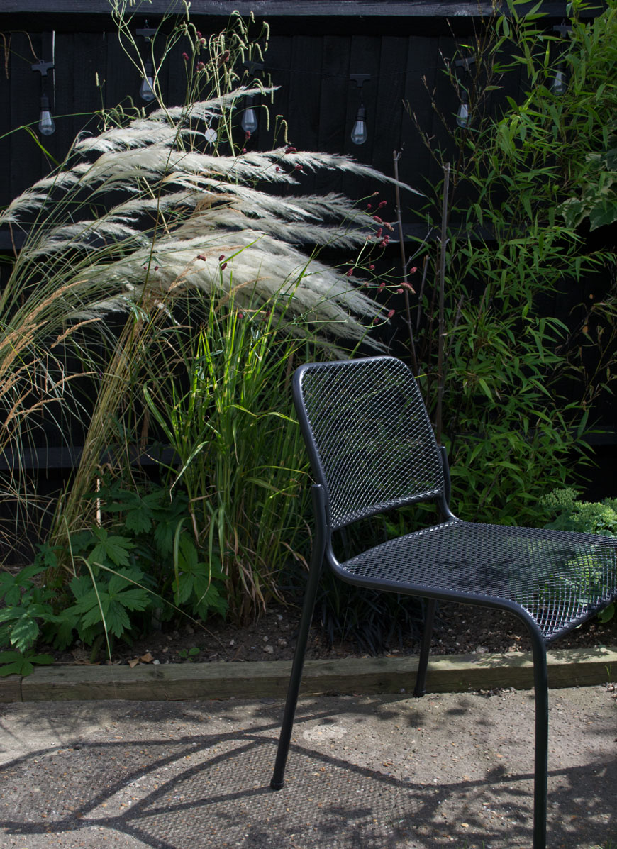 Black Mira outdoor chair with mesh seat by Skagerak sitting in front of an ornamental grass border.