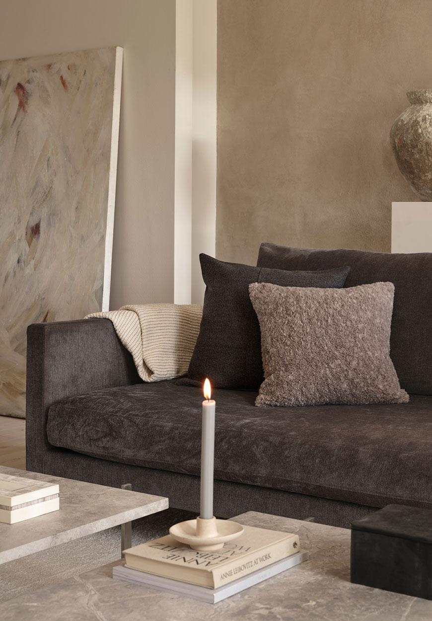 A contemporary brown sofa styled with textured neutral cushions and marble coffee tables for Zara Home.