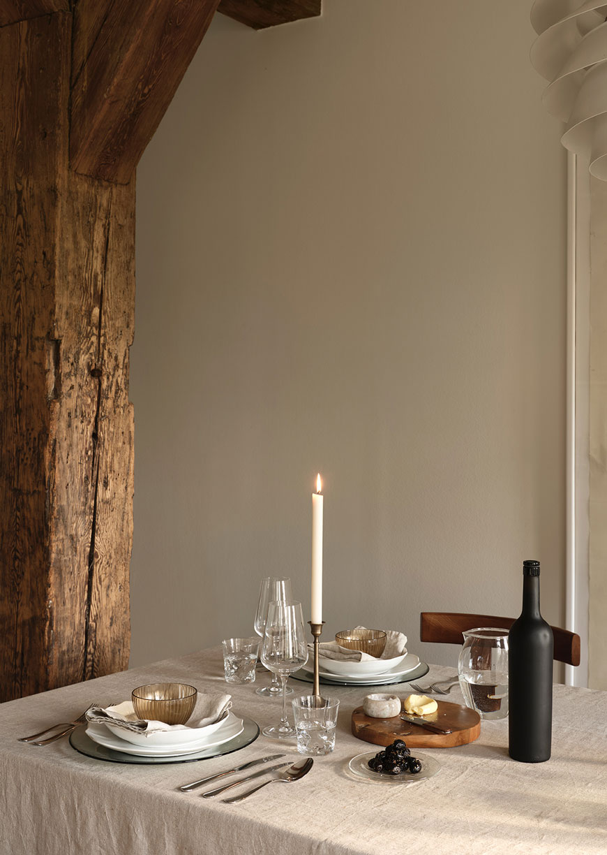 A rustic table set with linen table cloth, brass candlestick and amber glassware from Zara Home.