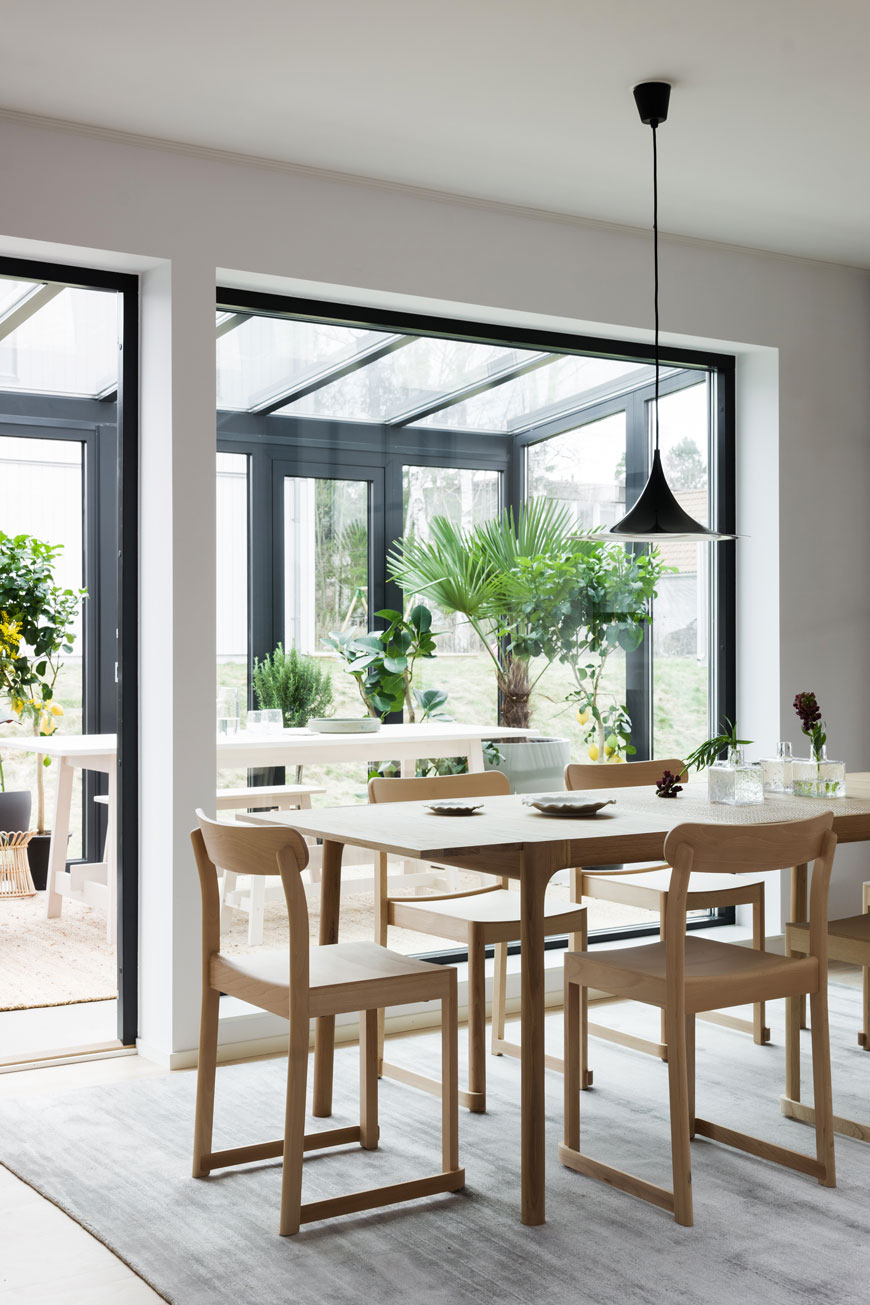 A beautiful, light filled dining room with oak dining table looks out into a contemporary garden room build by Blooc.