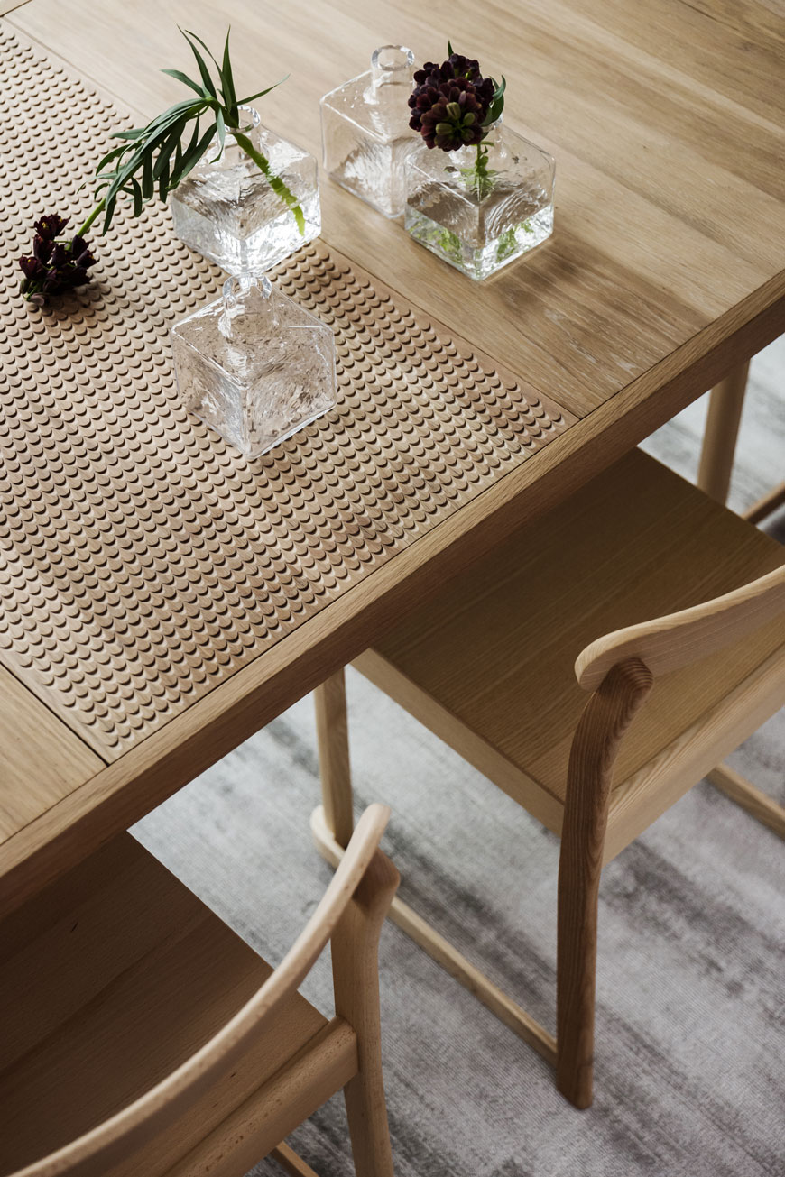 Details in an oak dining table styled with little bud vases inside the Parkhusen project by Blooc.