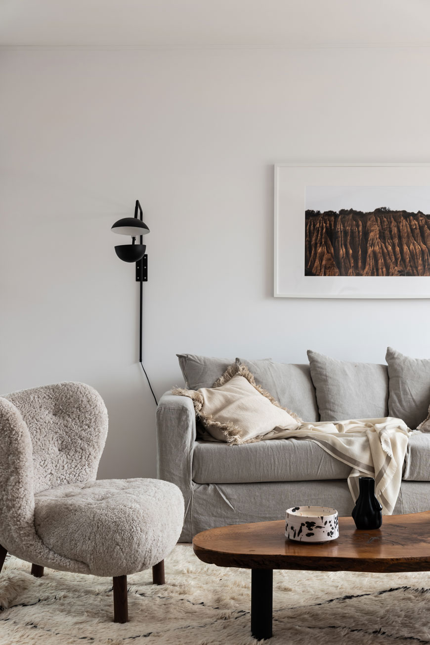 A cosy Nordic living room designed by Blooc with a grey linen sofa and fluffy Little Petra chair by &Tradition.