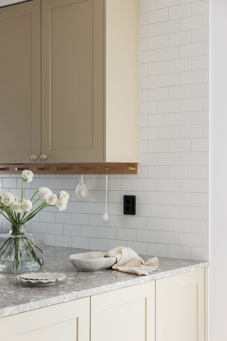 An off-white, cream kitchen with grey granite countertops, designed by Blooc Sweden.