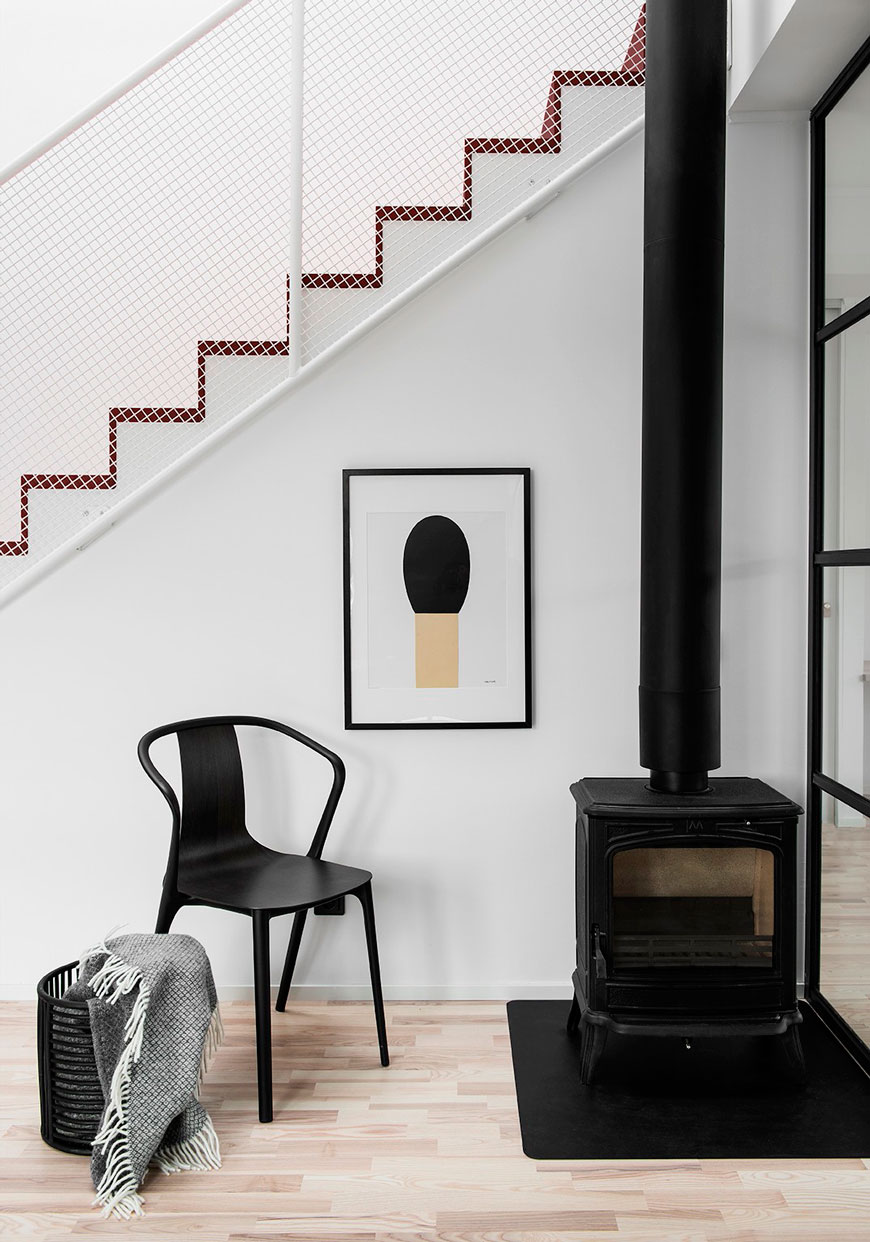 Architectural details show the minimal corrugated staircase and black wood burner, designed by Blooc.