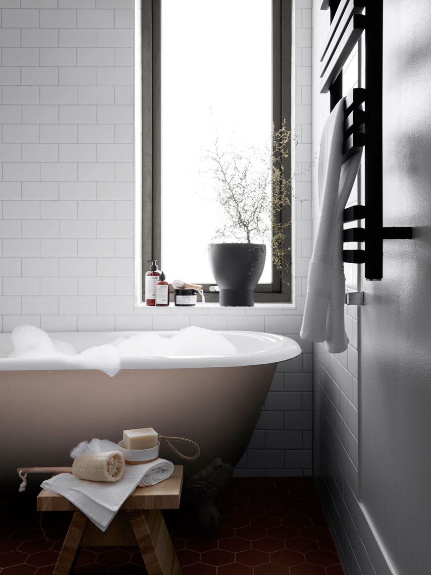 A freestanding roll top bath filled with bubbles waits in the bathroom of a Parkhusen home, designed by Blooc.