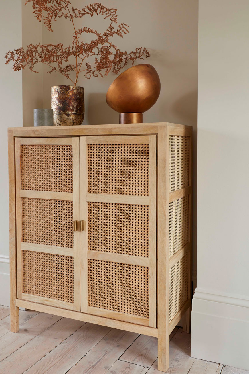 A French cane cabinet looks striking with a brass lamp on top for French Connection's Autumn-Winter collection.