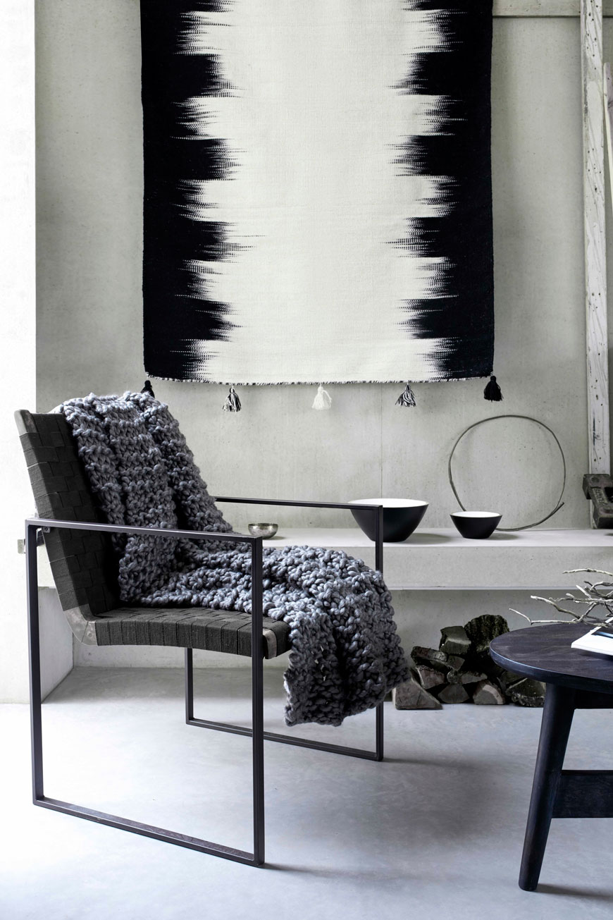 Striking black metal armchair in a modern concrete living space. styled with a grey chunky knit blanket.