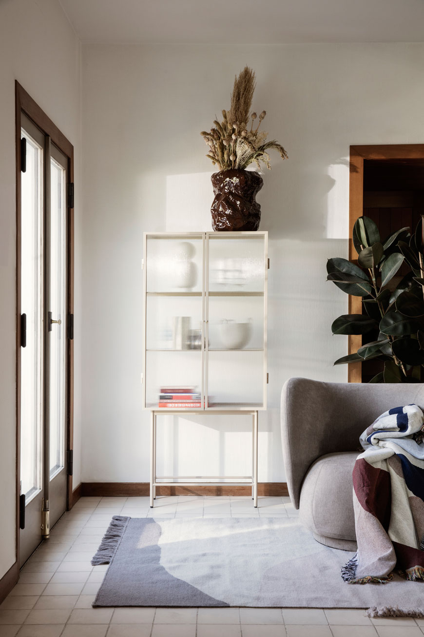 The Ferm Living Haze Vitrine in a Cashmere white styled in a Nordic living space with houseplants.