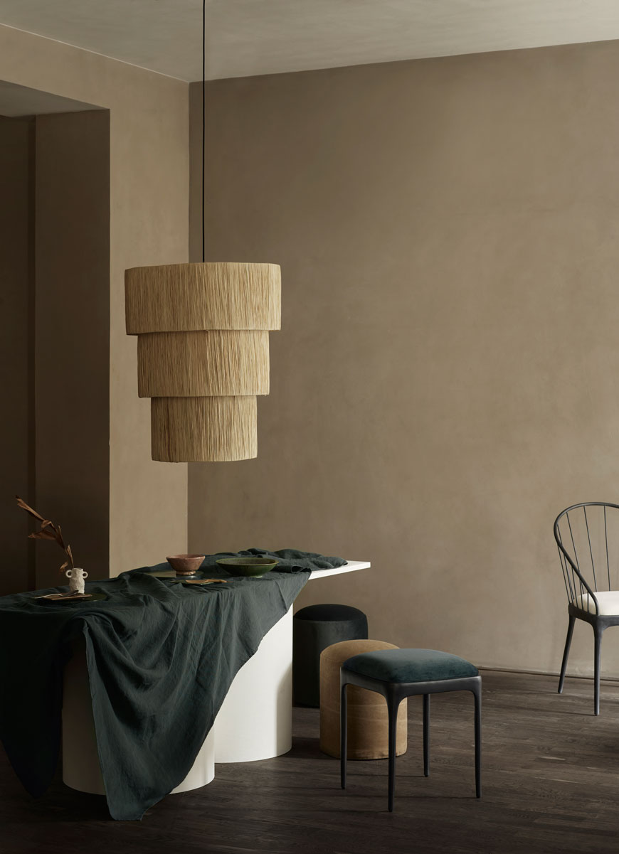 A tiered Tine K Home rattan pendant lamp looks striking over a table draped with deep blue linen.