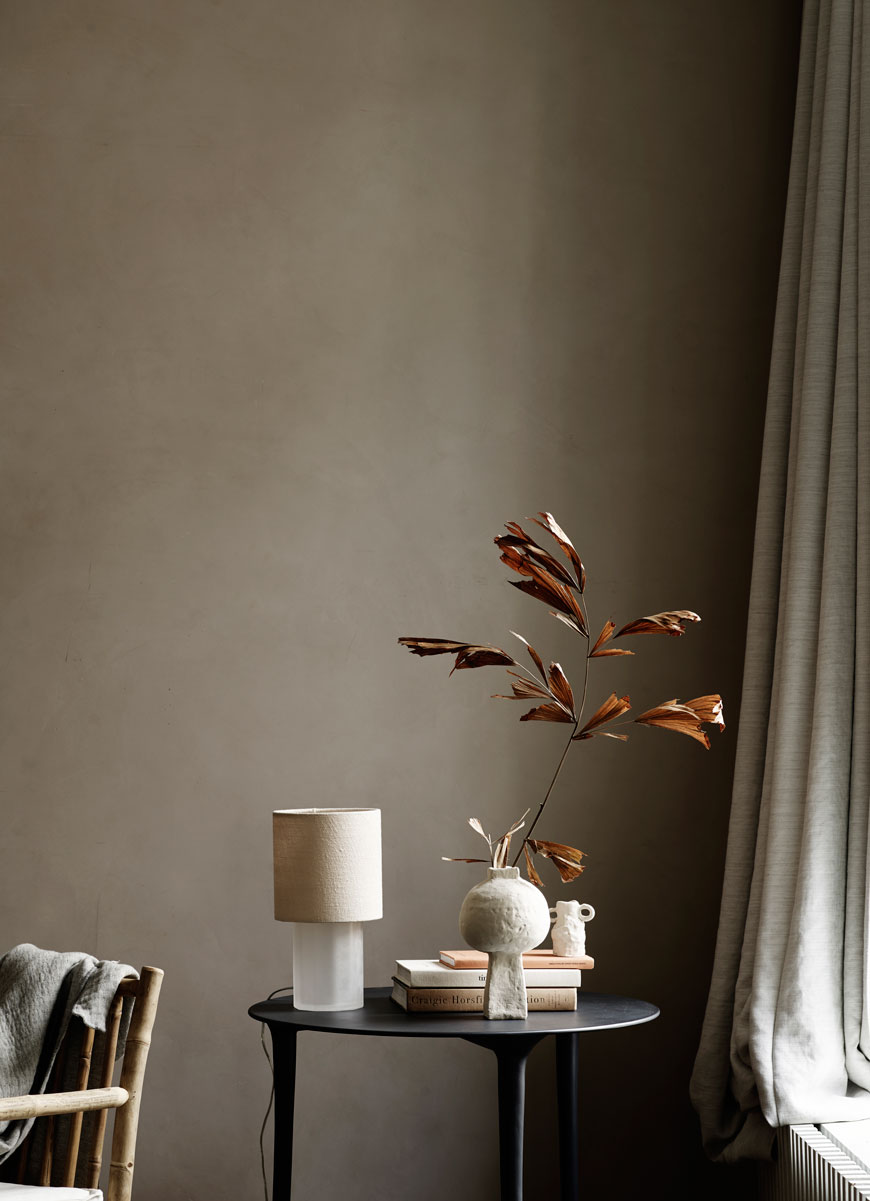 A simple black side table styled with autumnal leaves for Tine K Home's Autumn-Winter collection.
