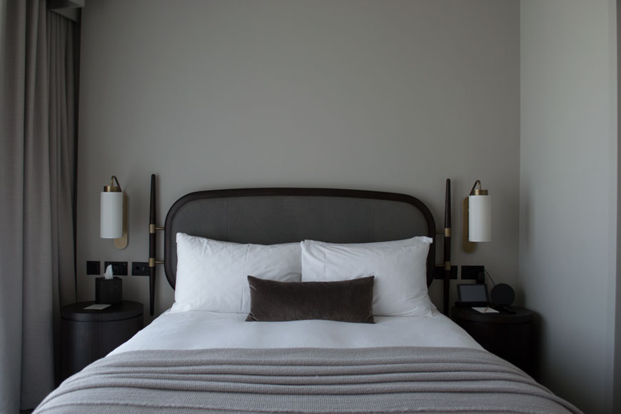 A view of the double bed in one of the grey toned bedrooms at The Stratford hotel, London.