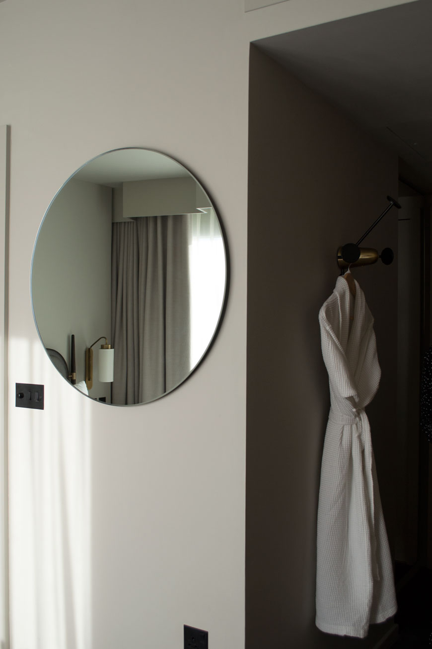 A brass bedside lamp and grey curtains reflected in a minimal, round mirror inside a hotel room.