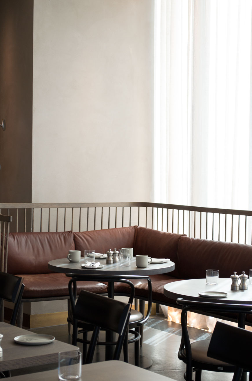 Wrap around wooden slatted breakfast bench with brown leather seat pads in the brasserie at The Stratford.