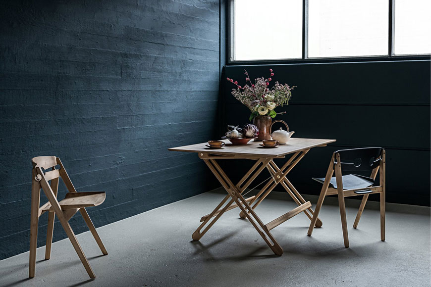 A dark and moody dining room styled with a Hagen folding dining table and chairs made from sustainable bamboo, from Pepper Sq.