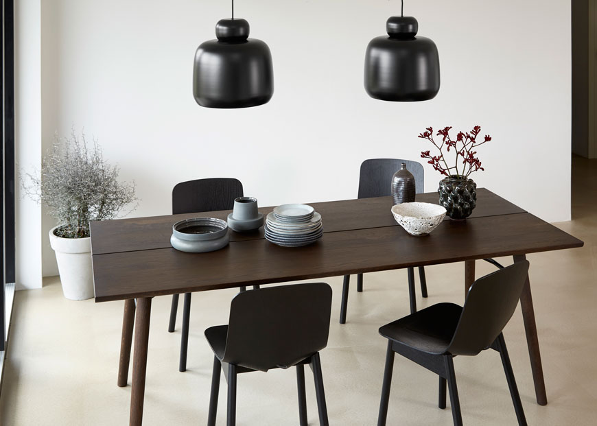 Dark smoked oaked Alley dining table designed by Woud set for entertaining paired with black pendant lights and black chairs.