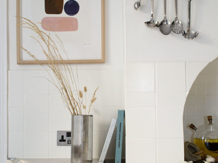 A blue and white Scandi style kitchen with grasses in a stainless steel vase and abstract print on the wall.