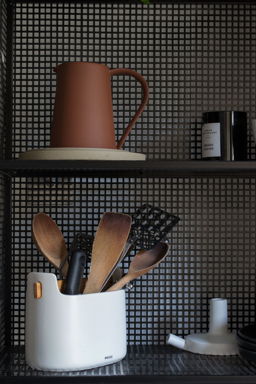 A close up of kitchen utensils stored in a minimal black wire kitchen unit, styled with Hasami plates and a terracotta pitcher.