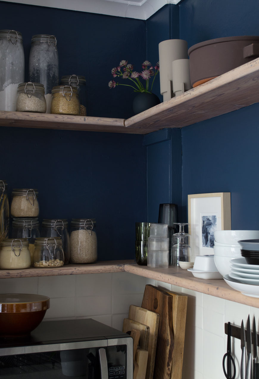 Open wood shelves styled with glass food jars and crockery in a dark blue and white Scandi style kitchen.