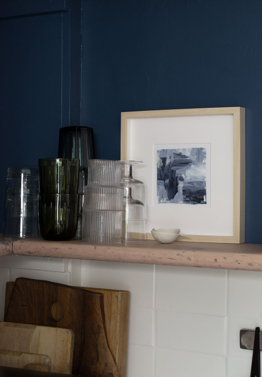 Open shelves in a blue and white Scandi style kitchen showcasing small kitchen storage ideas.