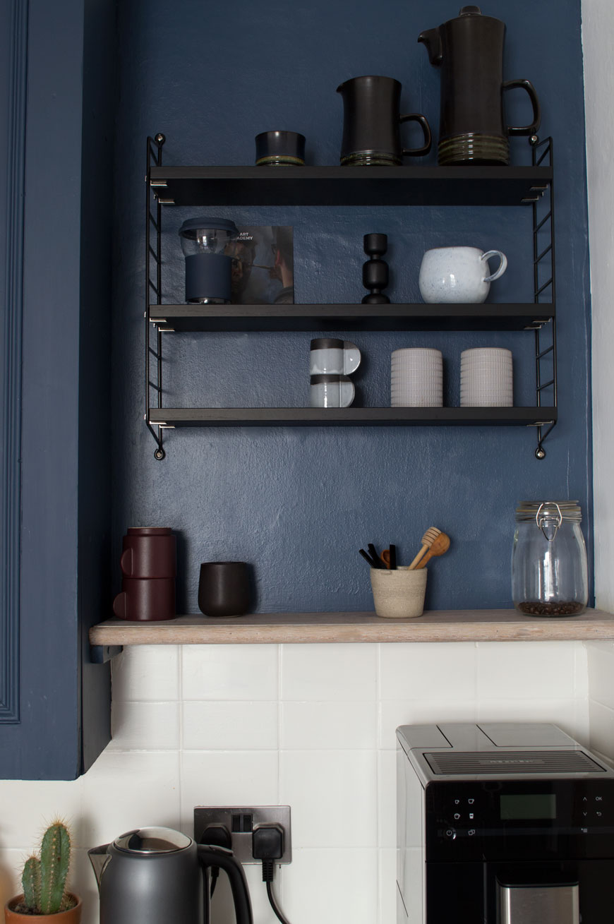 Black String Pocket shelves in a blue and white kitchen show simple small kitchen storage ideas.