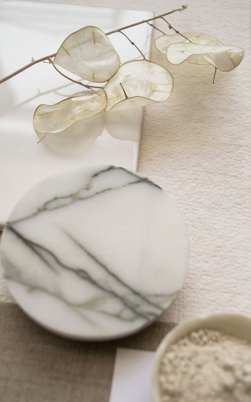 Translucent dried honesty or Lunaria, styled on a glazed white tile in a neutral moodboard.