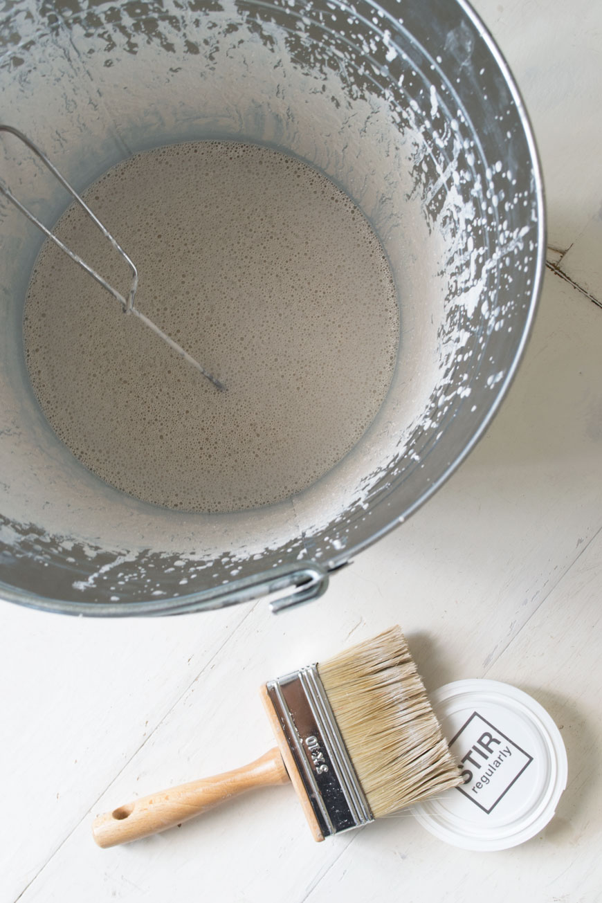Bauwerk Colour's Mykonos lime paint stirred and ready to paint from a bucket.