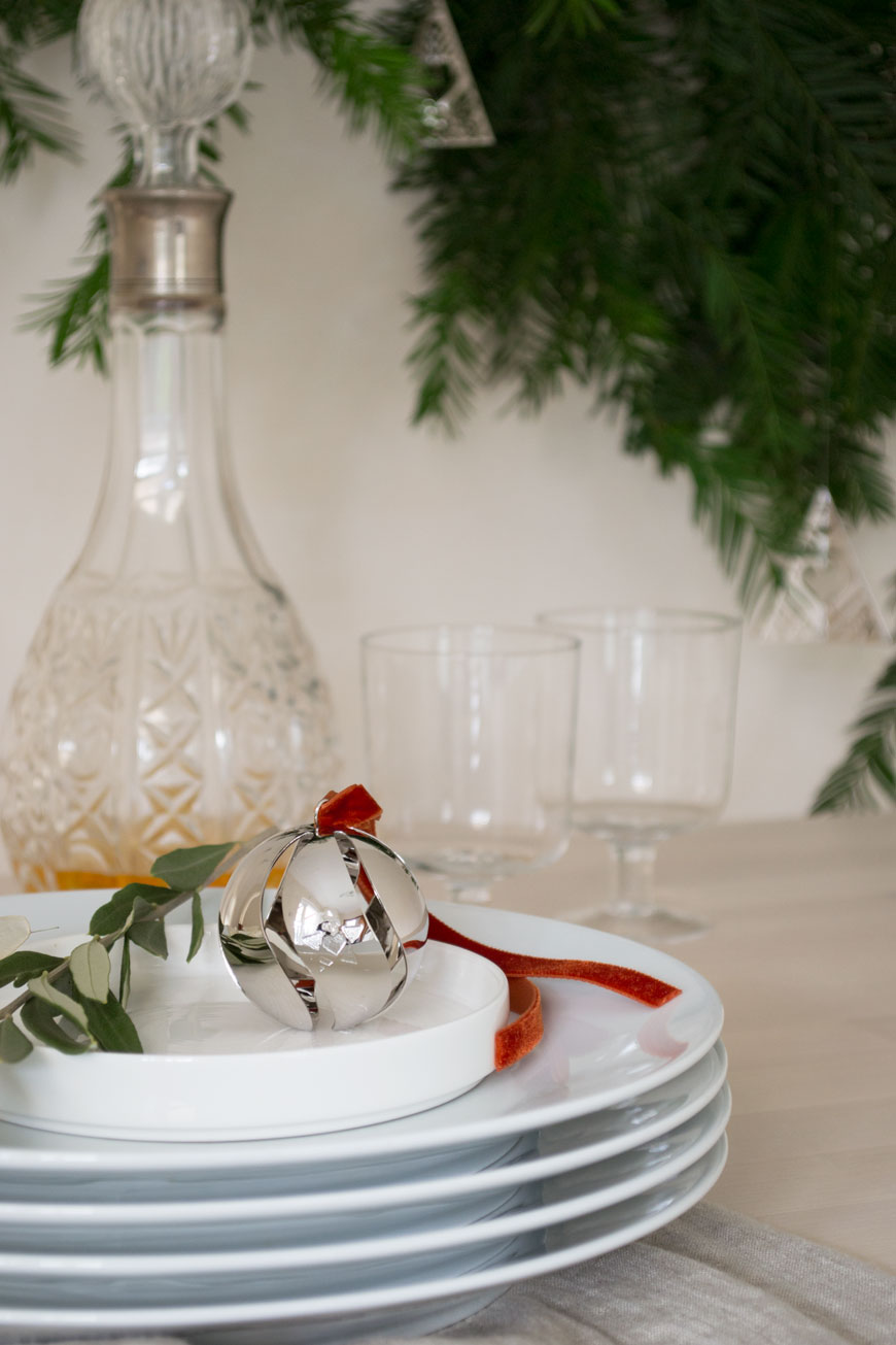 A sweet Ball Ornament styled on top of a stack of white dinner plate on the Christmas table.