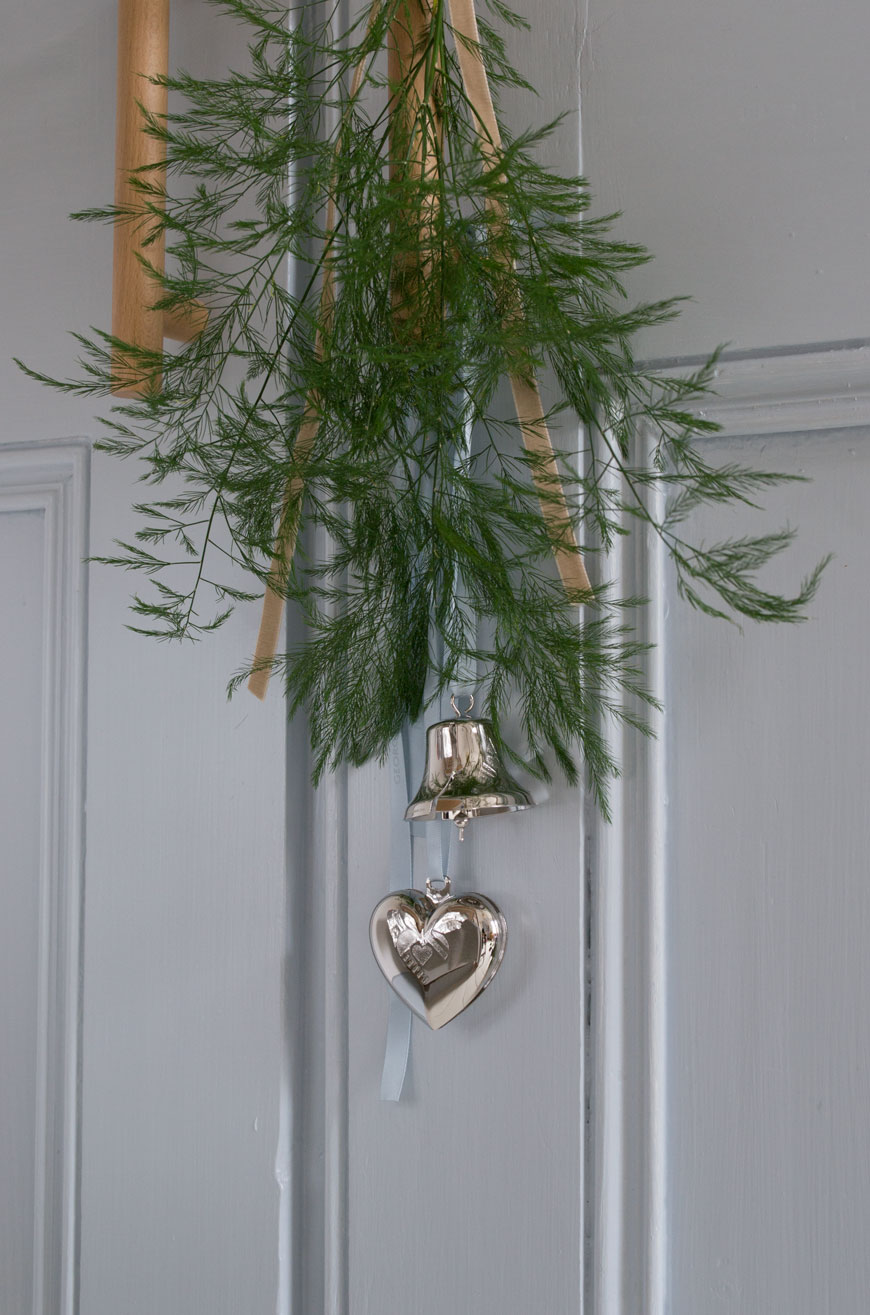 Sweet little festive details - a bunch of Christmas greenery tied with ribbon and little ornaments hung from a door handle.