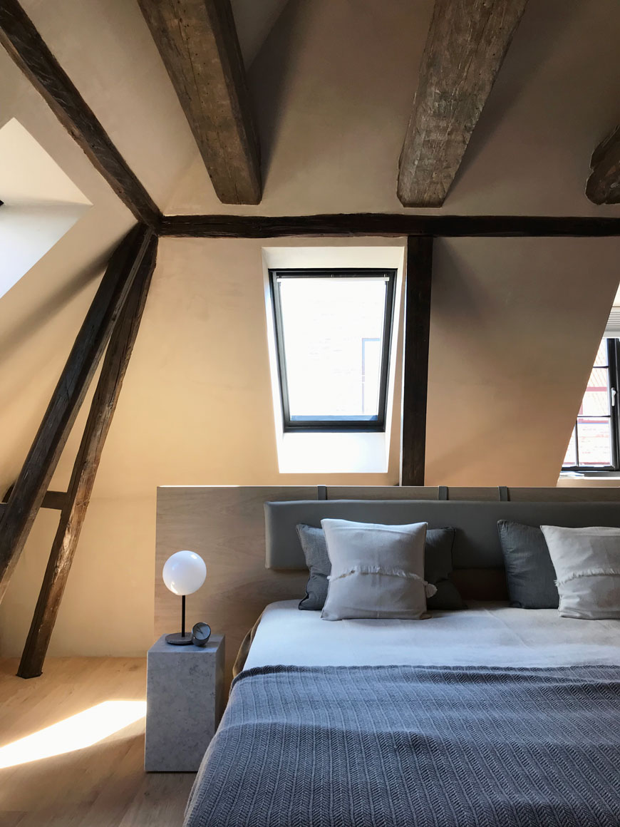 A light filled, cosy loft bedroom suite  with exposed timber beams dressed in blue and grey bedlinen at The Audo residence in Copenhagen.