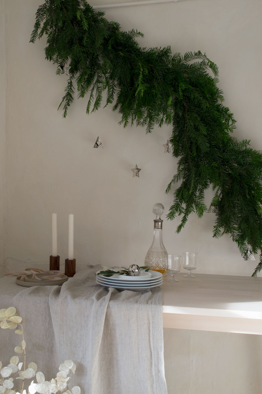 A Nordic Christmas table styled with a linen tablecloth, yew tree garland and Georg Jensen's Christmas Collectibles for 2019.