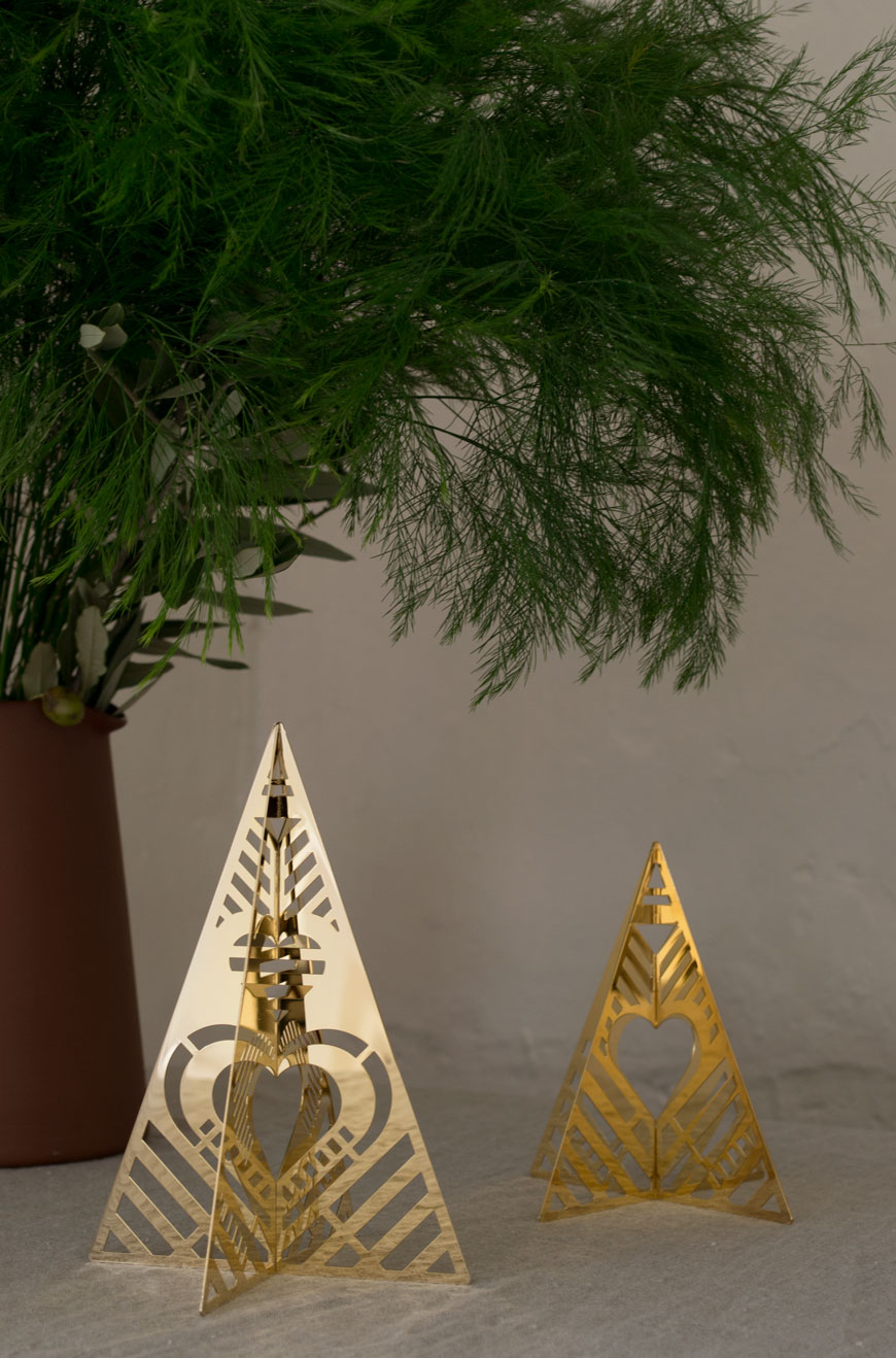 Gold plated Christmas tree ornaments on a natural linen table cloth.
