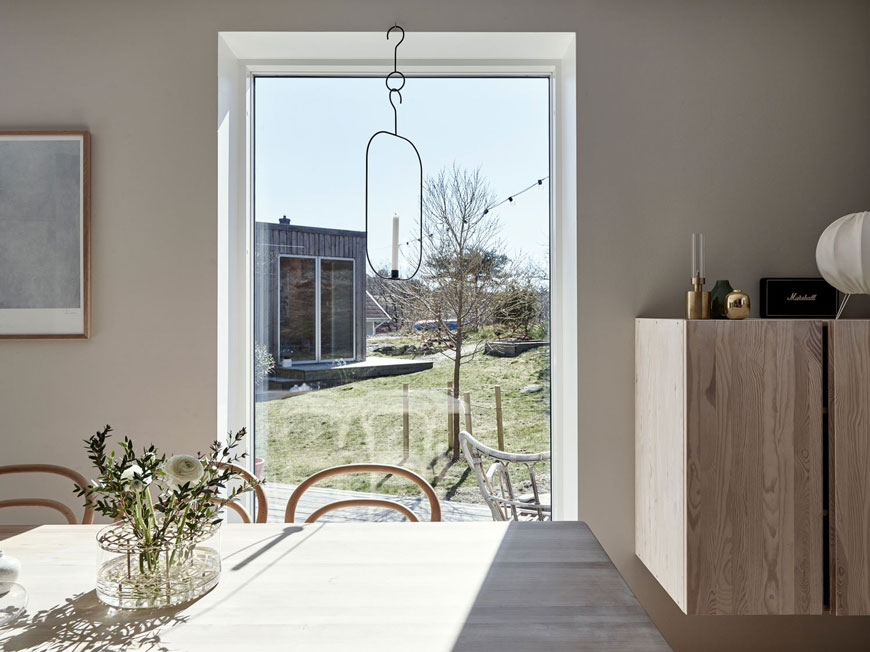 Looking out onto Brännö island from the full length window inside this minimal, light filled Scandinavian dining room.