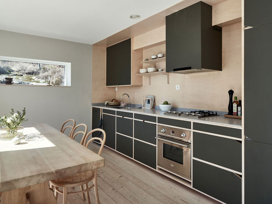 A Scandinavian open plan kitchen dining space with a plywood splashback and dark green kitchen cabinets.
