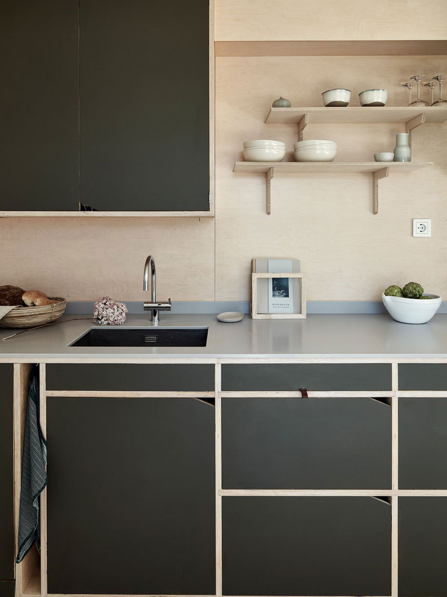 A contemporary, minimal plywood kitchen with dark green cabinets in an open plan architect designed family home in Sweden.