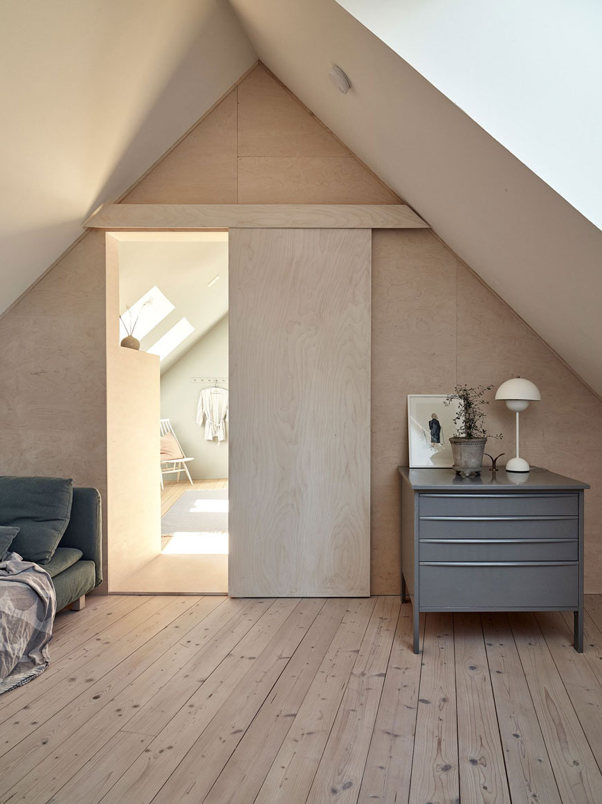 Looking into the bedroom with a plywood sliding door from the plywood clad snug of this architect designed Swedish island home.