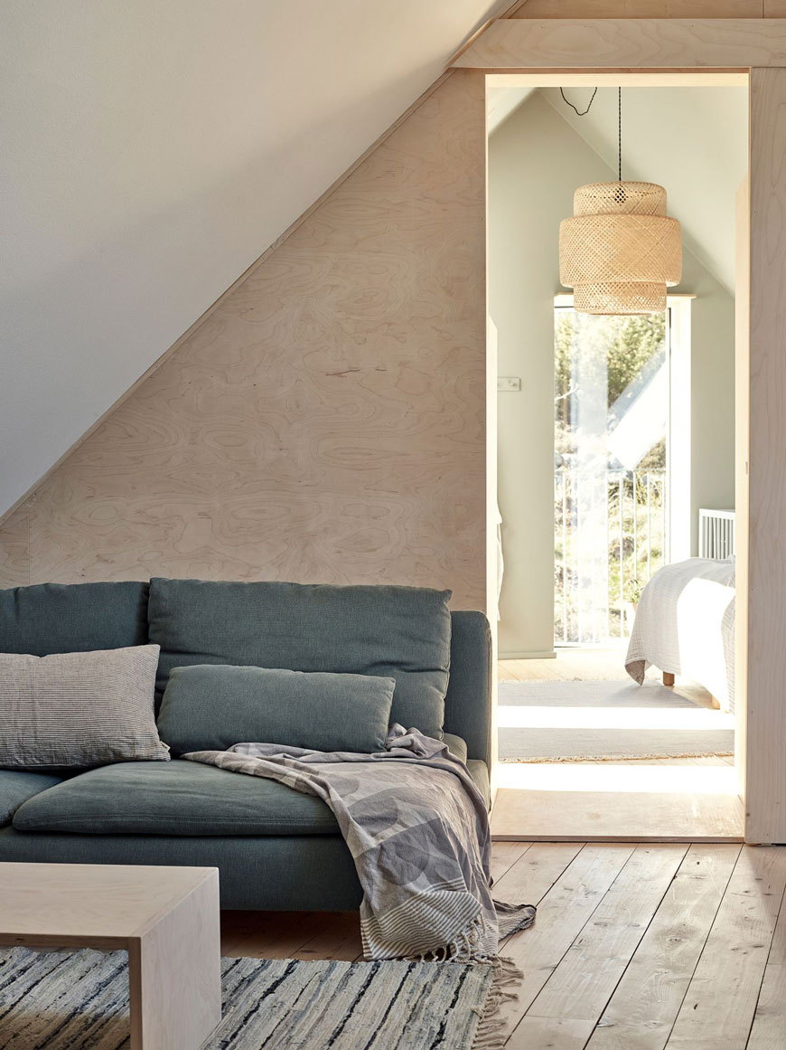A slouchy green sofa sits in the snug of this minimal, Scandinavian home looking into the bedroom styled with the popular Sinnerlig bamboo light shade from IKEA.