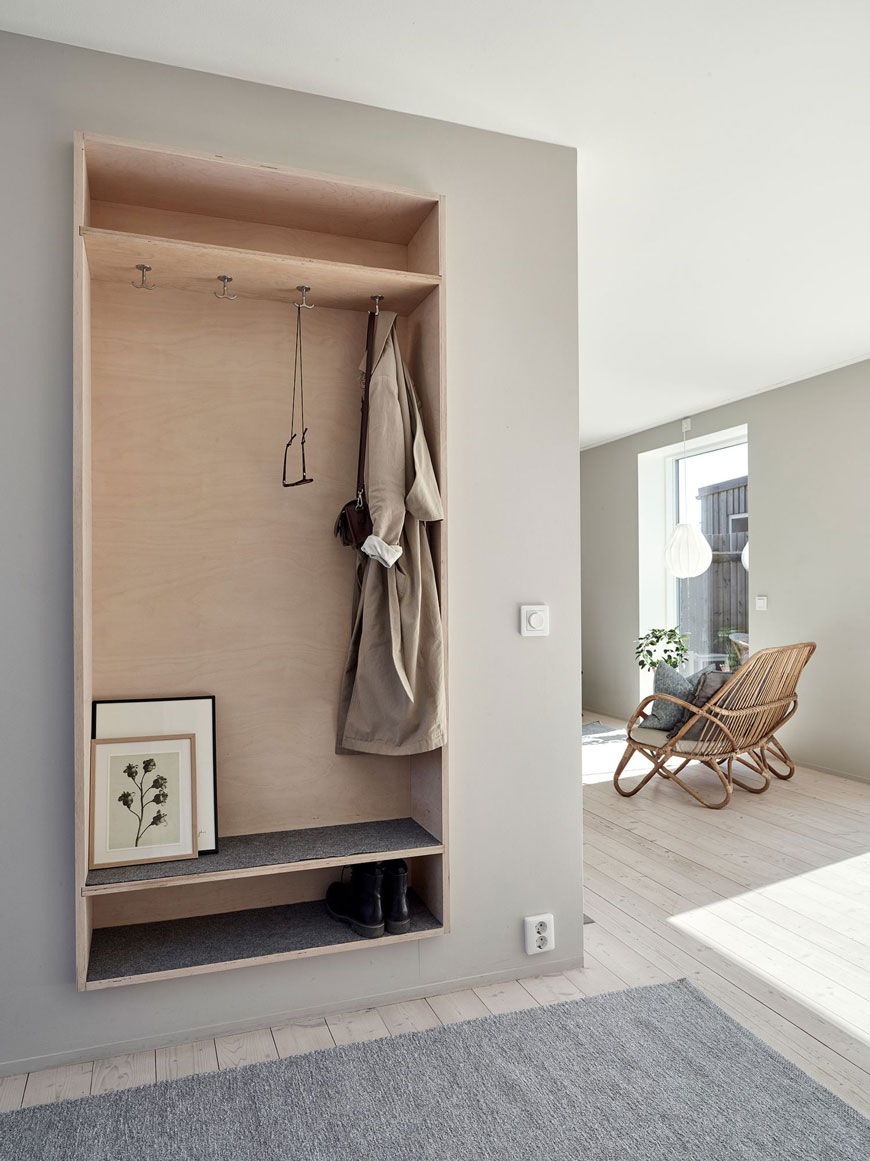 A wall mounted plywood open storage cupboard creates a hallway space in this architect designed family home in Sweden.