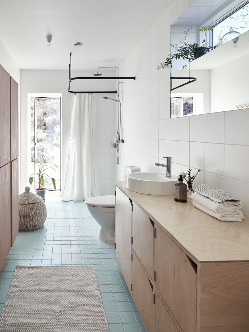 A bright, white tiled family bathroom with a square turquoise tiled floor and black hanging shower rail.