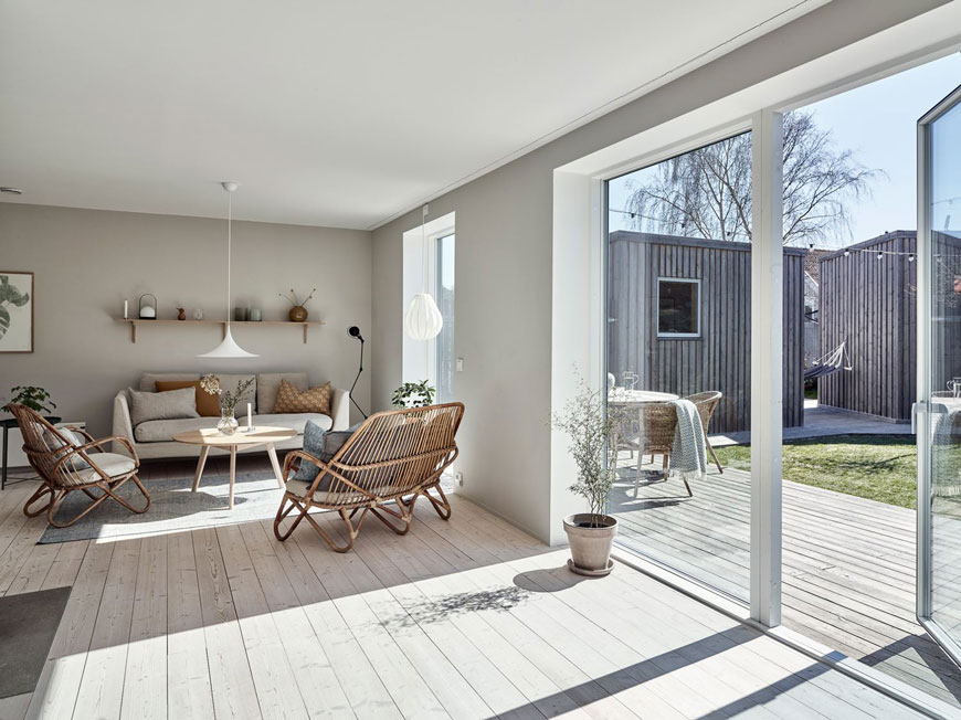 A stunning open plan L-shaped wood clad island home painted in light grey with minimal Scandinavian furniture.