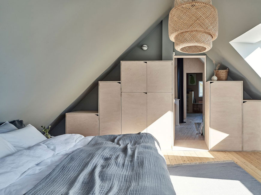 Built-in plywood box storage built into the eaves of this Scandinavian bedroom makes uses of the space.