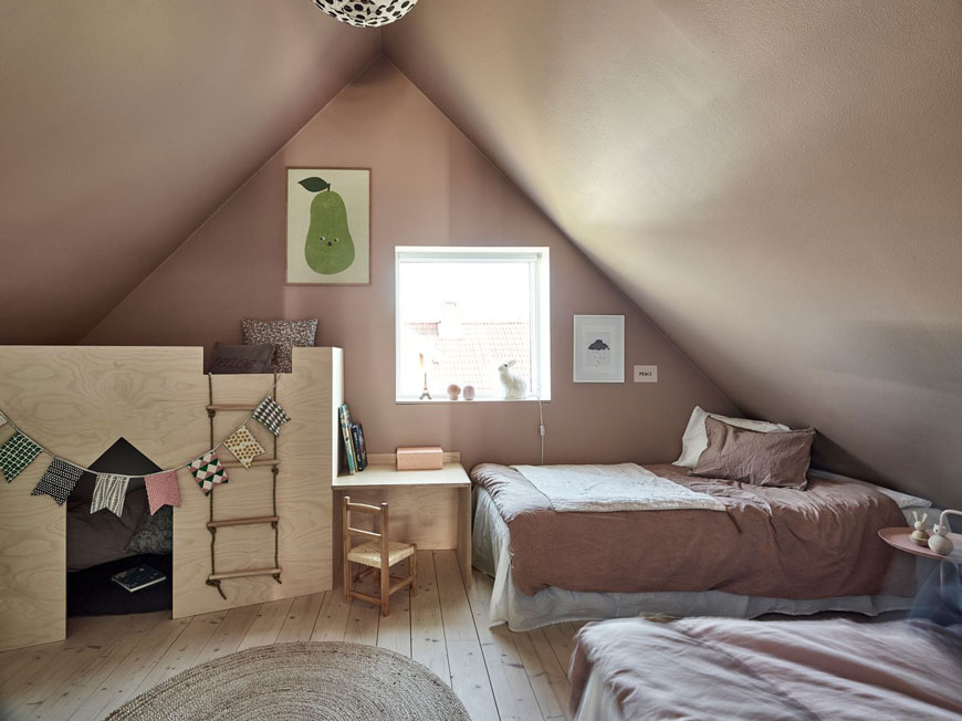 A soft pink and pine wood kids' bedroom in the eaves of an architect designed home has a sweet plywood