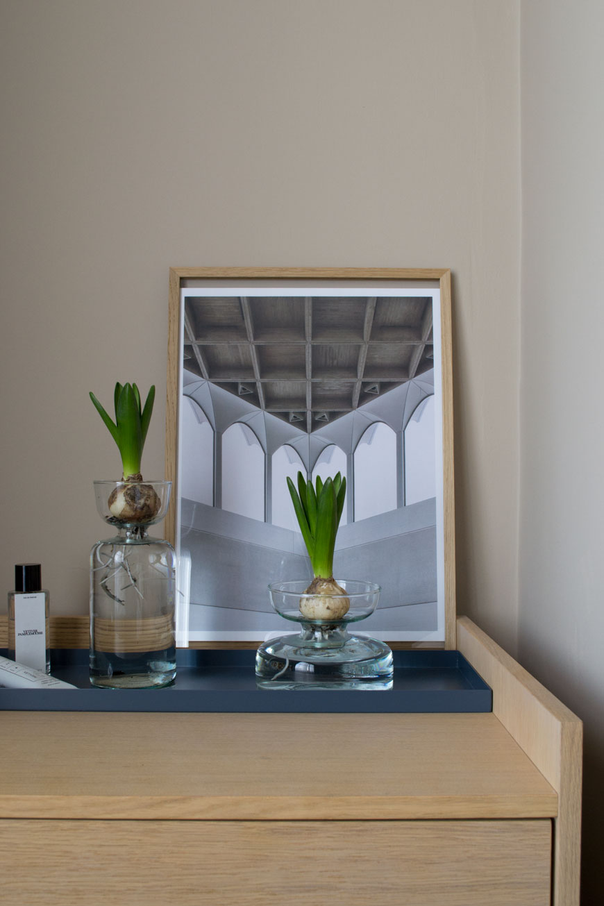 Two clear glass bulb planters from the LSA Canopy collection in a minimal, Nordic inspired beige bedroom.