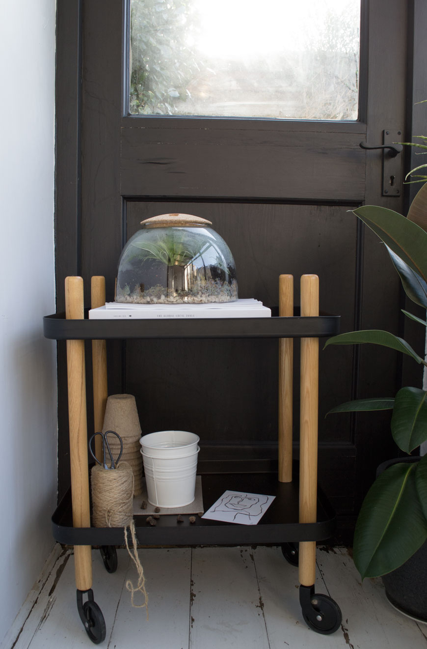 A monochrome sunroom is home to a closed humidity fern garden on top of a Normann Copenhagen Block Trolley in black.