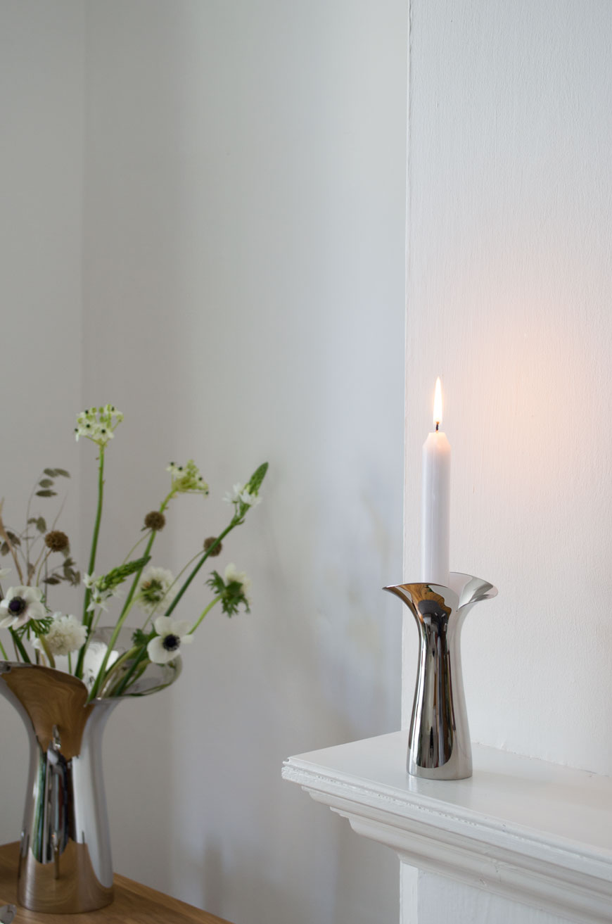 A solitary white candle sits in one of Georg Jensen's new Bloom Botanica candleholders in mirror polished stainless steel