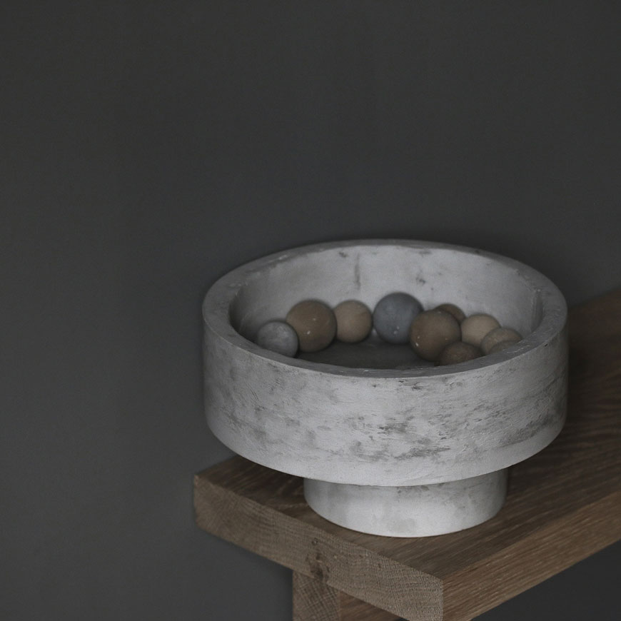 A collection of natural toned ceramic balls sit in the centre of an asymmetric grey pedestal bowl in a minimalist setting.